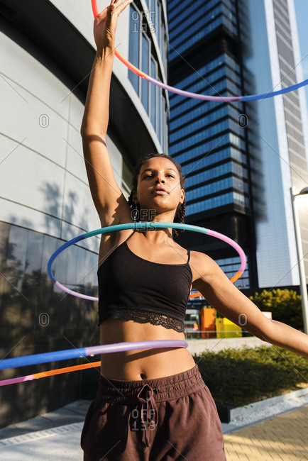 Sporty woman exercising with plastic hoops outside office buildings