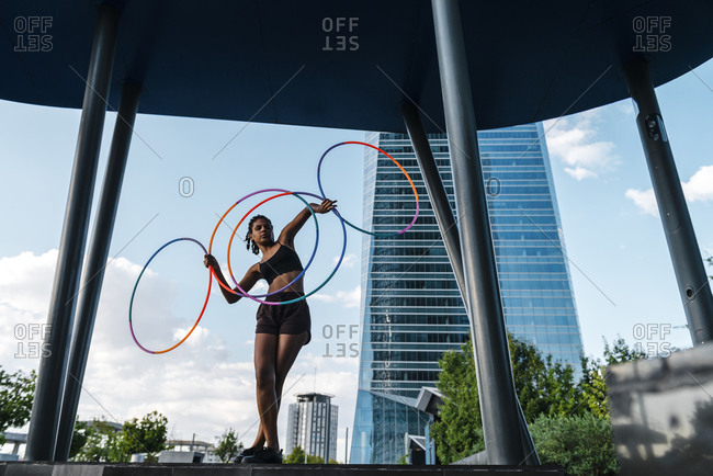 Sporty woman balancing plastic hoops in modern city