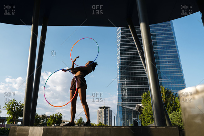 Sporty woman exercising with plastic hoops in modern city