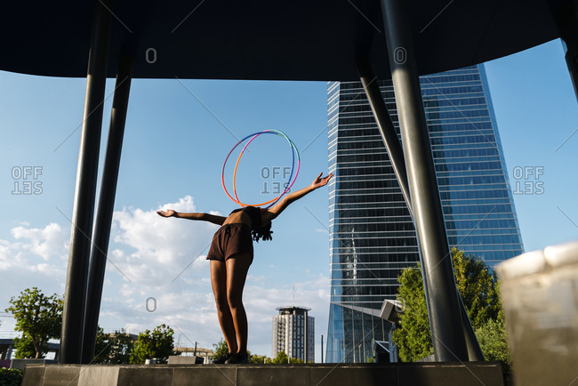 Sporty woman balancing plastic hoops on chest in modern city