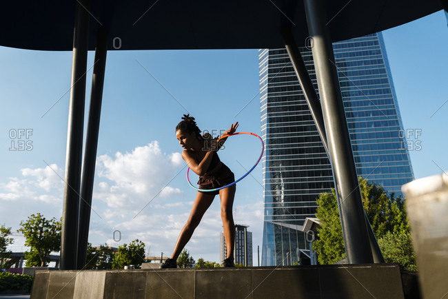 Sporty woman exercising with plastic hoops in modern city against blue sky