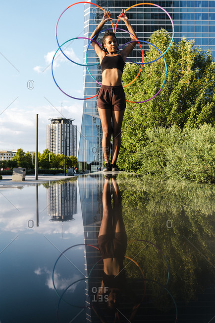 Sporty woman balancing plastic hoops on retaining wall in city