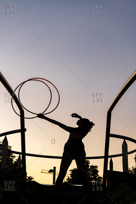 Silhouette sporty woman exercising with plastic hoops against clear sky during sunset