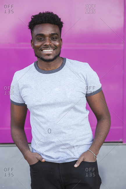 Smiling young man with hands in pockets standing against pink wall