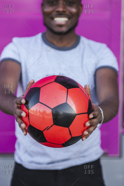 Close-up of young man holding soccer ball while standing against pink color