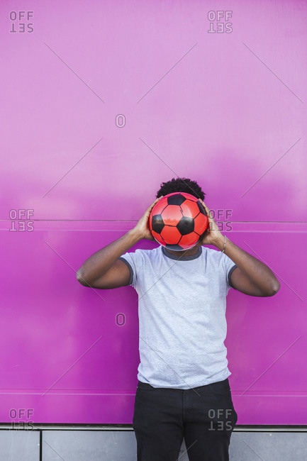 Young man holding soccer ball in front of face while standing against pink color