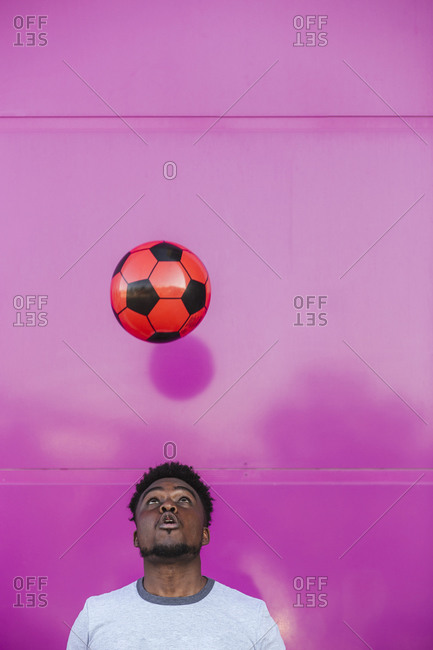 Young man juggling with soccer ball against pink wall in city