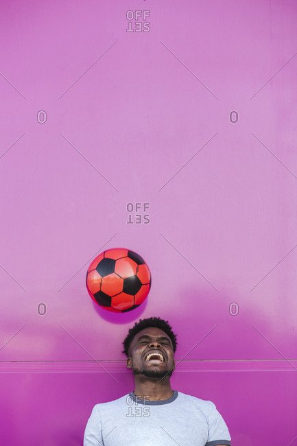 Cheerful young man juggling with soccer ball against pink wall in city