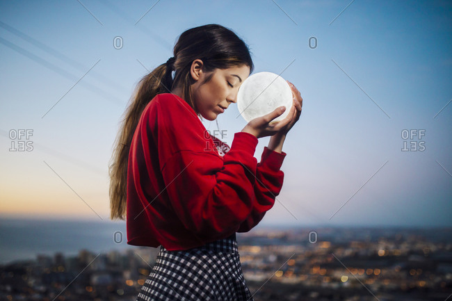 Young woman with eyes closed holding moon shape lamp against sky at dusk