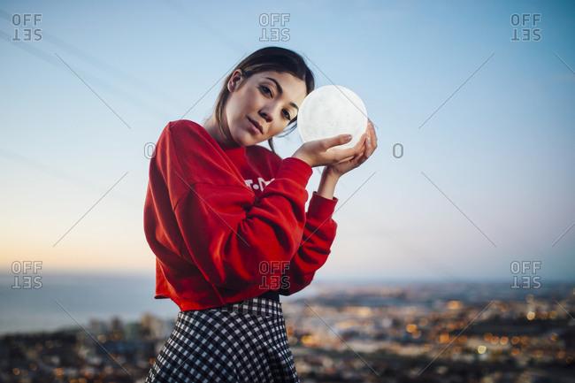 Woman holding illuminated moon shaped lighting equipment at dusk