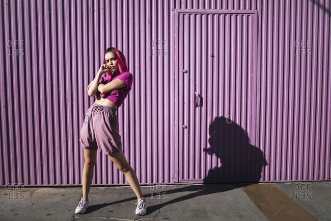 Pouting young dancer standing in front of purple wall