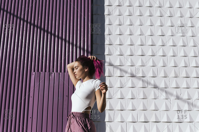Young woman with dyed hair moving with eyes closed in front of urban wall
