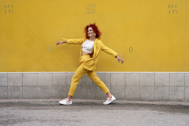 Energetic young woman in yellow suit running and jumping in front of yellow wall