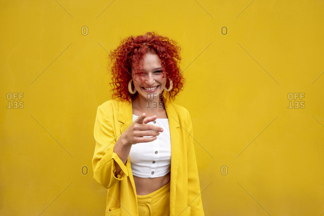 Happy young woman with red curly hair pointing with finger in front of yellow wall
