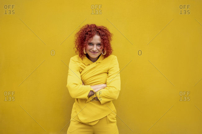 Happy young woman with red curly hair in front of yellow wall wrapping in jacket