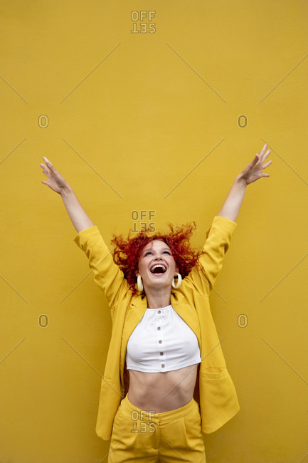 Exuberant young woman with red curly hair laughing in front of yellow wall