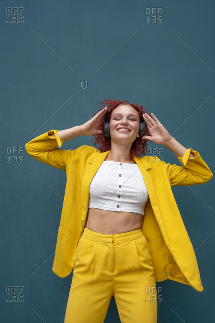 Young woman with red curly hair wearing headphones having fun listening music