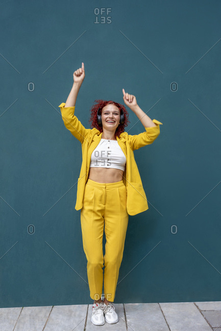 Young woman with red curly hair wearing headphones having fun listening music and dancing
