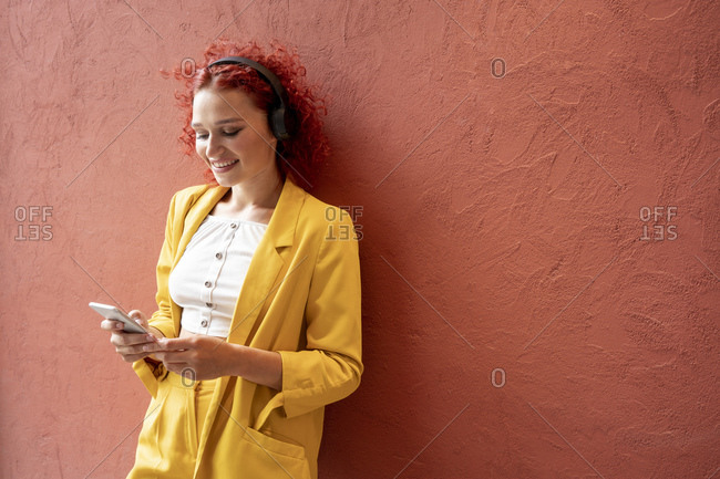 Young woman in yellow suit leaning against red wall- wearing headphones- using smartphone