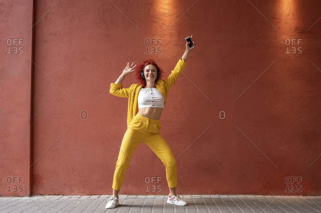 Young woman in yellow suit wearing headphones- dancing to music from her smartphone