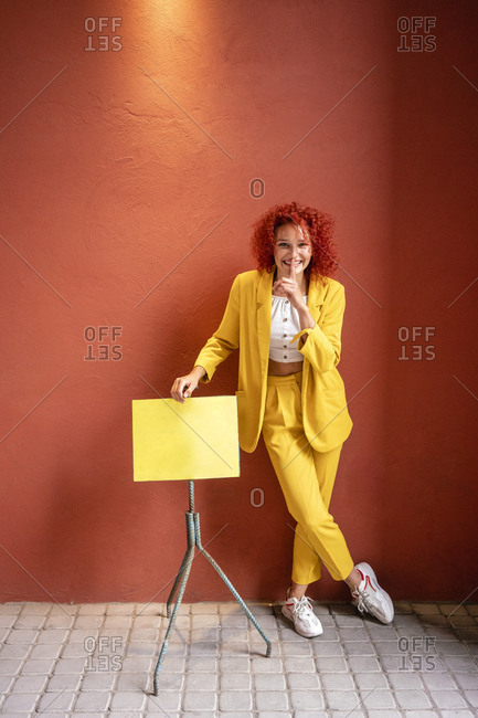 Young woman  in yellow suit leaning on music stand with finger on mouth