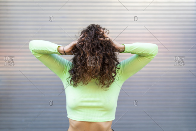 Young woman wearing green crop top with hands in hair posing against gray wall
