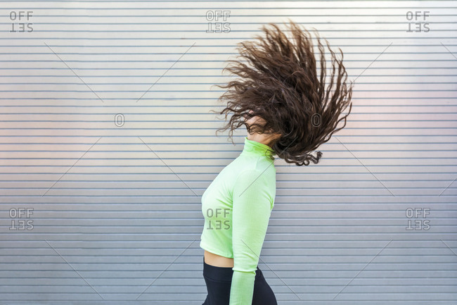 Young woman tossing hair while standing by gray wall