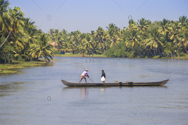 January 30, 2020: Men in dugout canoe, Backwaters, Kollam, Kerala, India, Asia