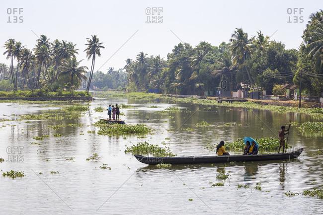 January 30, 2020: People crossing river in dug out canoe, Backwaters, Kollam, Kerala, India, Asia