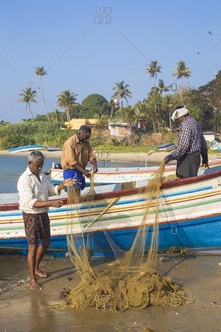 January 31, 2020: Fishing boats on beach with Tangasseri Lighthouse in background, Kollam, Kerala, India, Asia