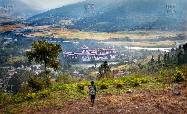 October 22, 2019: Young child looking down at Punakha Dzong, the second largest and second oldest dzong in Bhutan, Punakha, Bhutan, Asia