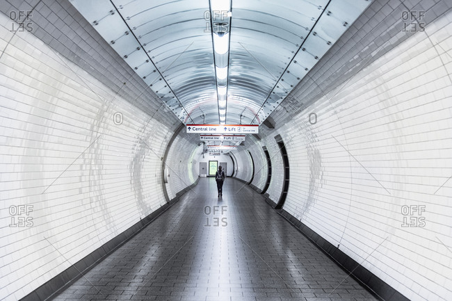 May 18, 2020: A single person walking along a corridor in an underground station during the Coronavirus lockdown, London, England, United Kingdom, Europe