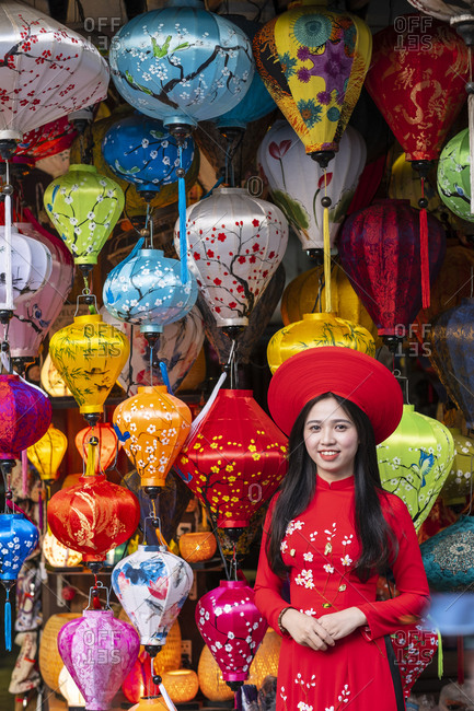 January 13, 2019: A young woman in traditional Vietnamese clothing standing outside a lantern shop, Hoi An, Vietnam, Indochina, Southeast Asia, Asia
