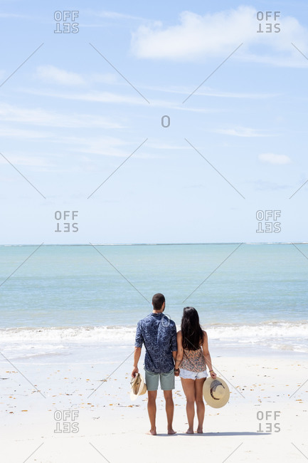 July 18, 2016: A good-looking Hispanic (Latin) couple on a deserted beach with backs to camera, Brazil, South America