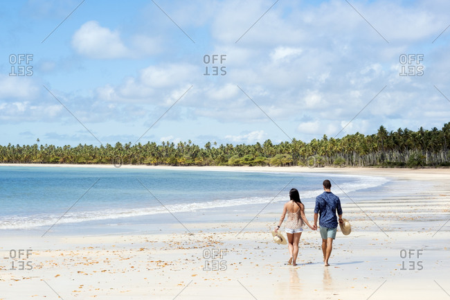 July 18, 2016: A good-looking Hispanic (Latin) couple walking on a deserted beach with backs to camera, Brazil, South America