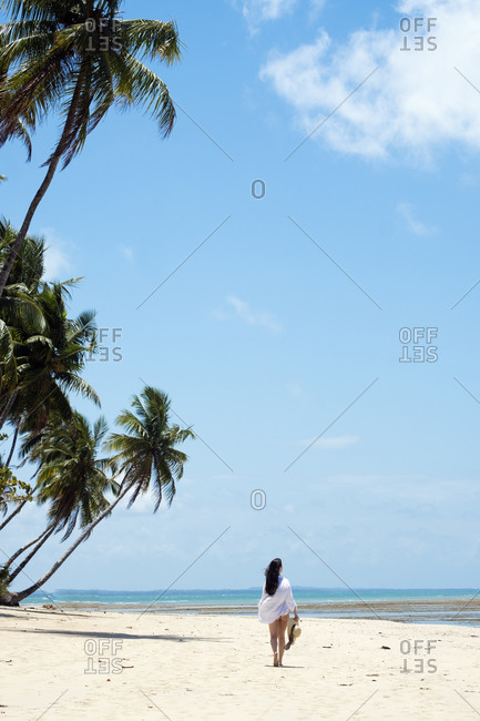 July 19, 2016: A young woman with brown hair wearing a white beach shirt and holding a hat walking along a tropical beach, Brazil, South America