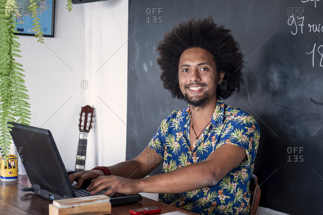 July 6, 2016: A Latin American man of African descent with Afro hair smiling to camera and sitting at a desk with a laptop computer, Brazil, South America