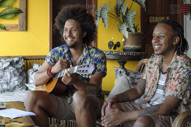 July 6, 2016: Two African Latin American friends sitting together in a living room and smiling off camera, one holding a classical guitar, Brazil, South America