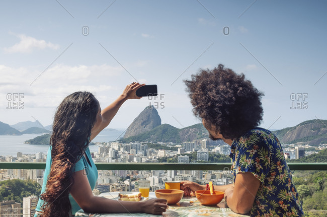 A multi-ethnic couple breakfasting and taking a mobile phone photo of Sugar Loaf and the Rio skyline, Rio de Janeiro, Brazil, South America