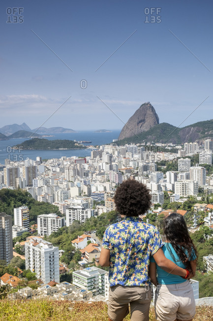 July 6, 2016: A multi-ethnic couple arm in arm looking out over Sugar Loaf mountain and the Rio skyline, Rio de Janeiro, Brazil, South America