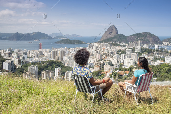 July 6, 2016: A multi-ethnic couple sitting together and looking out over Sugar Loaf mountain and the Rio skyline, Rio de Janeiro, Brazil, South America