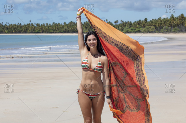 September 25, 2018: A beautiful Hispanic (Latin American) woman in her twenties smiling, holding a colorful shawl and standing on a deserted beach, Brazil, South America