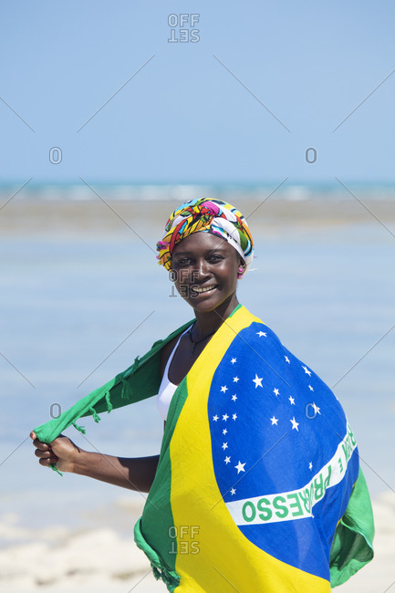 September 27, 2018: A young black Brazilian woman wearing a head scarf and a wrap showing the national flag, smiling and looking to camera, Brazil, South America