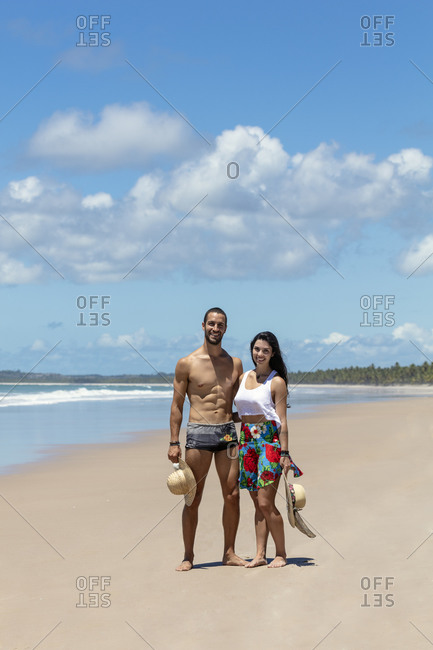 September 25, 2018: A good-looking Hispanic (Latin) couple on a deserted beach smiling to camera, Brazil, South America