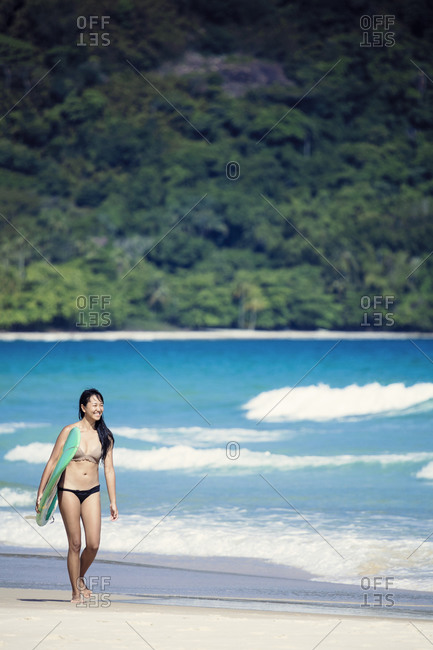 March 29, 2017: Beach shot of a Japanese Brazilian (Nipo-brasileiro) in a bikini carrying a surf board decorated with the Brazilian flag, Brazil, South America