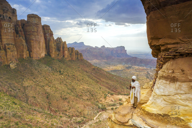 February 4, 2020: Orthodox priest admiring Gheralta Mountains from the entrance of Abuna Yemata Guh church, Tigray Region, Ethiopia, Africa