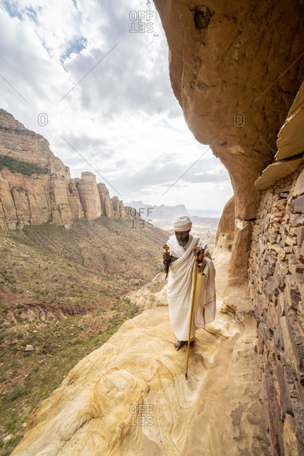 February 4, 2020: Priest holding the hand cross on rocks outside Abuna Yemata Guh church, Gheralta Mountains, Tigray Region, Ethiopia, Africa