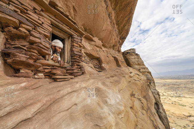 February 4, 2020: Priest looking out from a small window carved into rocks in Abuna Yemata Guh church, Gheralta Mountains, Tigray Region, Ethiopia, Africa