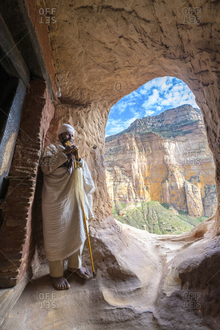 February 4, 2020: Ethiopian Orthodox priest holding the hand cross at entrance of Abuna Yemata Guh church, Gheralta Mountains, Tigray, Ethiopia, Africa