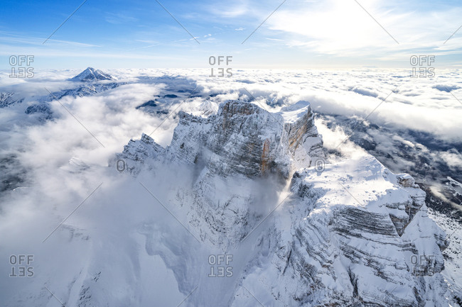Snow capped Monte Pelmo emerging from clouds, aerial view, Dolomites, Belluno province, Veneto, Italy, Europe